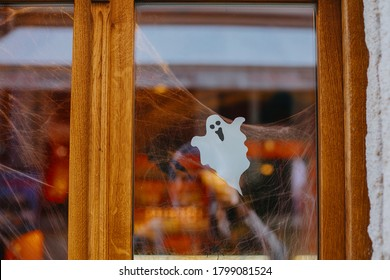 Halloween street decor. Paper cut ghost and cobweb on door or window at store, festive decoration of city street. Happy Halloween