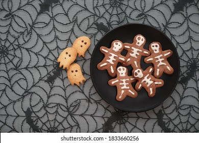 Halloween sweets, cookies and biscuits handmade and baked in black dishes with cobweb on the background