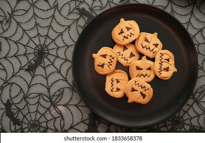 Halloween sweets cookies handmade and baked, pumpkin shaped with textile cobweb on the background.