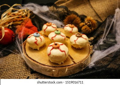 Halloween sweets eye shaped and biscuits in a mummy shaped shortcrust pastry, decorated with sugar paste, pumpkins, bats, spiders, fruits on juta fabric