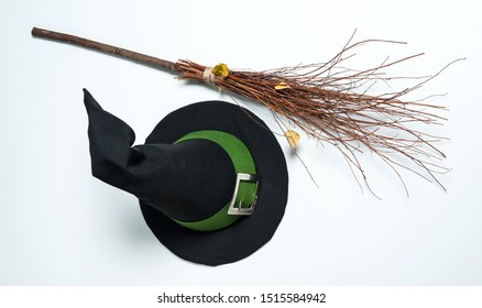 Halloween Symbols.  A pointed magic hat with a green ribbon and a silver buckle, a witch's broom on a white background. Isolated.
