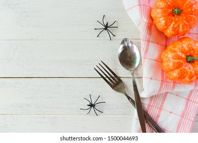 Halloween table setting decoration accessories holiday dinner with spider spoon fork and pumpkin on tablecloth in the white wood table , top view copy space