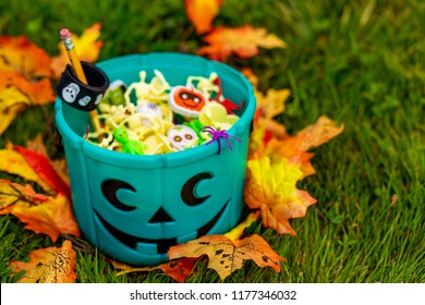 Halloween teal basket full of non-food treats. Halloween Party Favors for kids with food allergy. Teal pumpkin. the concept of health for children in the Halloween season
