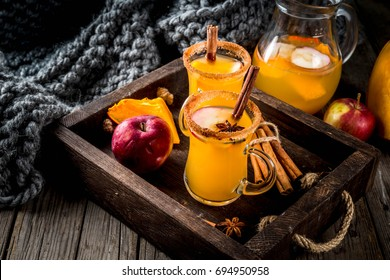 Halloween, Thanksgiving. Traditional autumn, winter drinks and cocktails. Spicy hot pumpkin sangria, with apple, cinnamon, anise. In tray, rustic wooden table, glass mugs. Selective focus copy space.