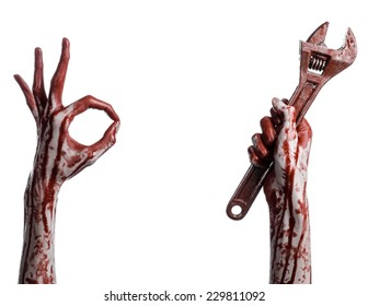 Halloween theme: bloody hand holding a big wrench on a white background