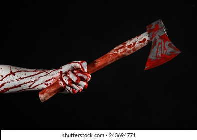 Halloween theme: bloody hand holding a bleed butcher's ax isolated on black background in studio