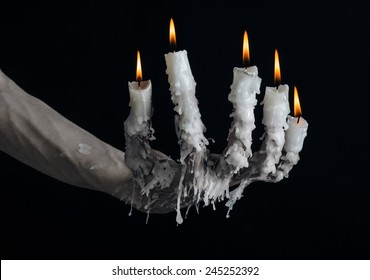 Halloween theme: on the hand wearing a candle and dripping melted wax on black isolated background