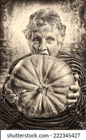 Halloween theme. Portrait of an old woman eating a big ripe pumpkin freshly harvest in autumn. Studio shoot and sepia toned image.