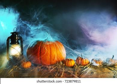 Halloween theme with pumpkins under spider web with vintage lamp against smoky dark background