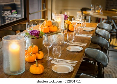 Halloween theme table with pumpkins, candles, cutlery and shiny glasses