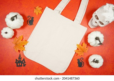 Halloween theme trick or treat canvas tote bag mockup with white skull pumpkins on a bright textured orange background. Product mock up with negative copy space.