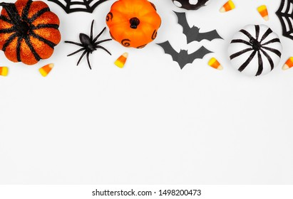 Halloween top border of pumpkins, candy and decor. Flat lay over a white background with copy space.