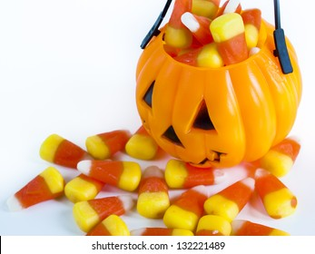 Halloween treat bag filled with candy corn candies on white background.