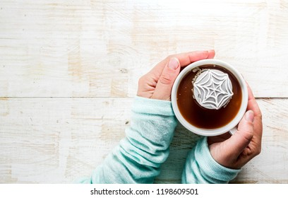 Halloween treats concept, Girl drinking hot chocolate with marshmallow decorate spider cobweb, hands in the picture, top view, copy space
