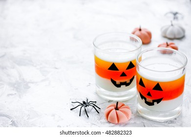 Halloween treats for kids - delicious white orange jelly on white table. Halloween food background blank space for text