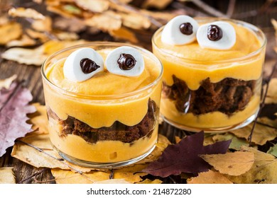 Halloween treats, little monster dessert with chocolate cookies and pumpkin mascarpone cream  topped with big marshmallow eyes