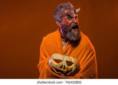 Halloween trick or treat. Demon surprised in blanket with jack o lantern. Man devil hold pumpkin on orange background. Darkness and light concept. Satan with bloody horns, beard, blood, wounds.