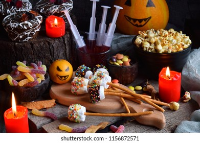 Halloween trick or treat party. Funny delicious sweets and pumpkin on wooden background - muffins, cupcakes, marshmallows, popcorn, juice, jellies, candy.