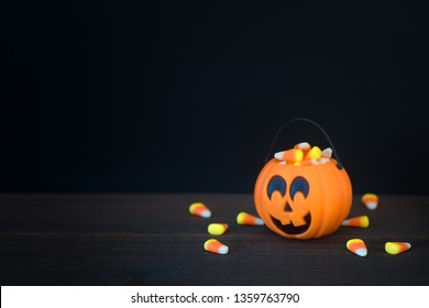 Halloween Trick or Treat Pumpkin filled with candy corn on dark wood table and with black background with room or space for copy.  Horizontal