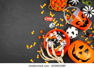 Halloween trick or treat side border with jack o lantern pails and assorted candy. Top view on a black background with copy space.