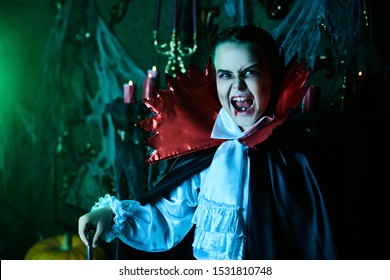 Halloween. Vampire boy in the old castle shows his fangs. Children's horror movie.