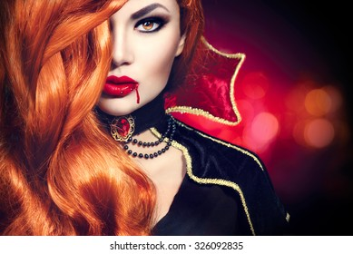 Halloween Vampire Woman portrait. Beautiful Glamour Fashion Sexy Vampire Lady with long red hair, beauty make up and costume