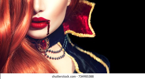 Halloween Vampire Woman sexy lips with dripping blood. Beautiful Glamour Fashion Sexy Vampire Lady with long red hair, beauty make up and costume. Isolated on black background. Vampire mouth.