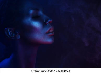 Halloween Vape Party, Nightlife. Beautiful Sexy Young Woman with glamorous mystical makeup vaping in Nightclub, exhaling smoke. Girl smoking vaporizer in Club. Blue mystic smoke