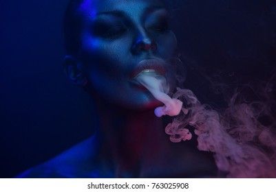 Fiesta de Vape de Halloween, Vida nocturna. Hermosa Mujer Sexy Joven con glamuroso maquillaje místico en neón de Nightclub, exhalando humo. Chica vaporizadora fumando en el Club. Humo místico azul