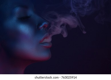 Halloween Vape Party, Nightlife. Beautiful Sexy Young Woman with glamorous mystical makeup vaping in Nightclub neon, exhaling smoke. Girl smoking vaporizer in Club. Blue mystic smoke