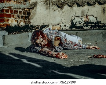 Halloween war soldier with bloody wounds. man crawling on paving asphalt. Zombie hipster with red blood. Vampire in torn clothes on grunge background. Halloween holiday celebration concept.