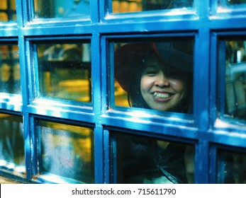 Halloween Witch. Beautiful Asian woman in witch hat and costume sitting armchair on Blue iron frame window Foreground for Halloween concept. with copy space.
