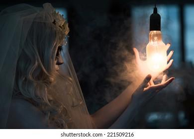 Halloween witch. Beautiful woman wearing santa muerte mask casting spell near light bulb