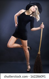 Halloween witch with a broom isolated over black background.