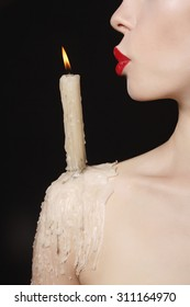halloween witch with candle.beautiful Woman lips blowing to the candle.candle wax on her body
