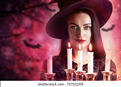 Halloween Witch with candles and magic lights in a dark forest. Beautiful young surprised woman in witches hat and costume holding pumpkin. Wide Halloween party art design