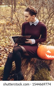 Halloween Witch with a carved Pumpkin in a autumn forest. Beautiful young woman in witches dress costume holding pumpkin.  Halloween party