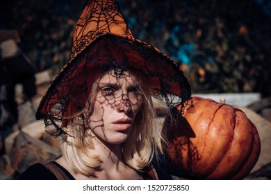 Halloween Witch with a carved Pumpkin and knife. Fantasy horror Halloween. Halloween art design. Happy Halloween Witch with bright make-up