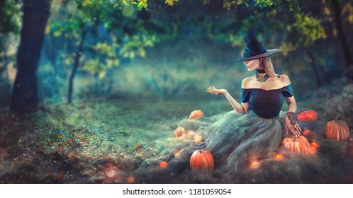 Halloween Witch with a carved Pumpkin and magic lights in a dark forest at night. Beautiful young woman in witches costume pointing hand, holding some product, advertising. Halloween party art design