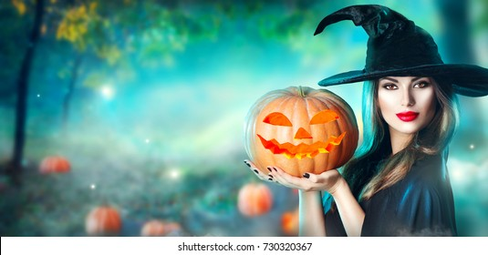 Halloween Witch with a carved Pumpkin and magic lights in a dark forest. Beautiful young surprised woman in witches hat and costume holding pumpkin. Wide Halloween party art design
