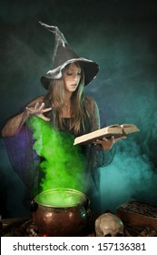 Halloween witch cooking a potion in a copper cauldron