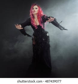 Halloween Witch creates magic. Attractive woman with red hair in witches costume standing outstretched arms, strong wind
