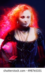 Halloween Witch creates magic. Attractive woman with red hair in witches costume, blur motion effects