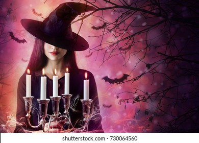 Halloween Witch in a dark forest. Beautiful young woman in witches hat. Halloween art design