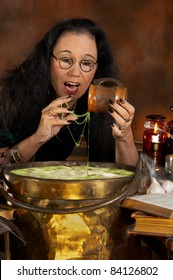 Halloween witch dripping green slime into her cauldron