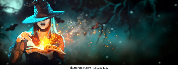 Halloween Witch girl with magic Book of spells portrait. Beautiful young woman in witches hat conjuring, making witchcraft. Over spooky dark magic forest background. Wide Halloween party art design