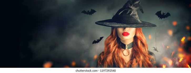 Halloween Witch girl portrait. Beautiful young woman in witches hat with long curly red hair and bright lips. Over spooky dark magic forest background. Wide Halloween party art design