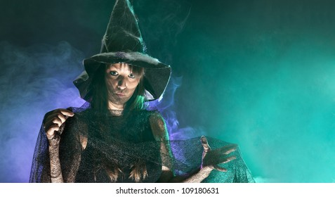 Halloween witch, green and blue smoke background