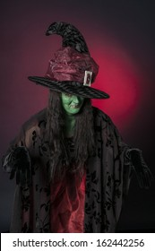 Halloween witch with green face on red background