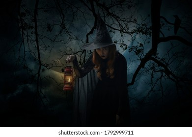 Halloween witch holding ancient lamp standing over dead tree, crow, birds, full moon and spooky cloudy sky, Halloween mystery concept